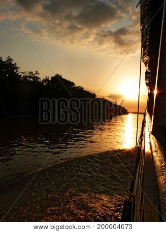 Sunset going up the Amazon River. A Texas Rose sky and an amazing sun reflection on the water. The Amazon Forest is only a black silhouette on the background. The picture was taken in Paranà, Brazil