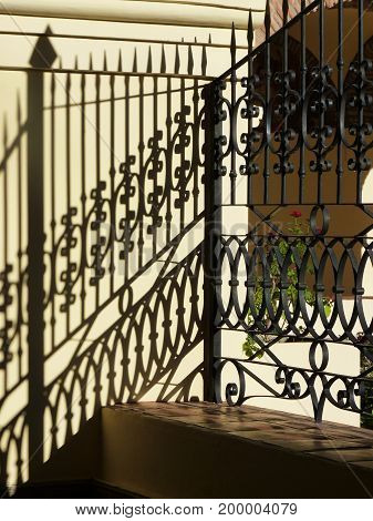 Ornamental railing and shadows on a portico. Little rose on the background. The picture was taken in Salta, Argentina