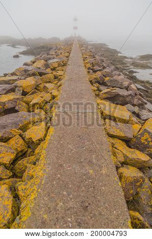 Long stone pathway with large boulders on both sides covered in yellow moss on a foggy day leading up to a lighhouse on the island of St Pierre and Miquelon.