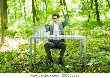 Portrait Of Young Handsome Succesful Manager In Suit Working At Laptop At Office Table With Raised H
