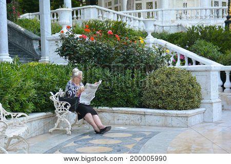 Baku, Azerbaijan, May 29, 2017. Elderly woman reads a newspaper in park