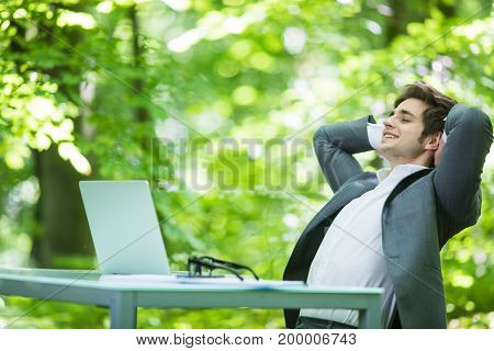 Portrait Of Young Handsome Business Man In Suit Relax At Laptop At Office Table Hands Over Head In G