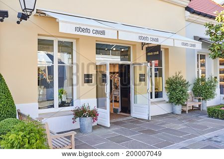 PARIS FRANCE - MAY 10 2017 : Roberto Cavalli boutique in La Vallee Village. RC is one of the most sought-after fashion designer known for his awe-inspiring creations in denim and in printed leather