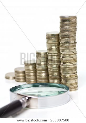 coins stacks with magnifying glass on white background