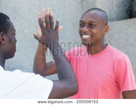 Laughing african american man giving high five outdoor in the summer