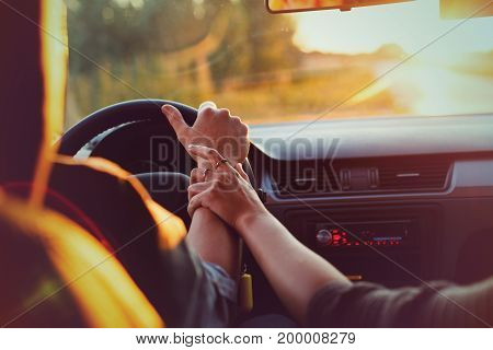 The couple drives the car on the way to the sunset. He drives the car she holds his hand. Shooting close-up. Support for loved ones. Go to the sunset. Travel of lovers.