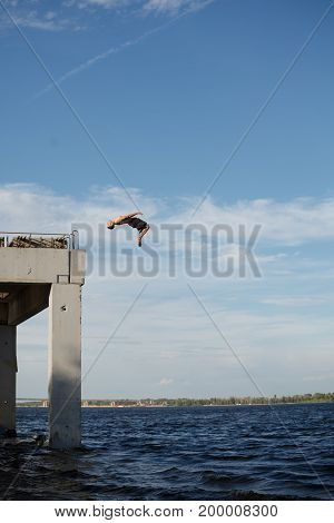 A man is jumping into the sea from a high pier. Adrenaline and extreme sports. Back somersault in the jump.