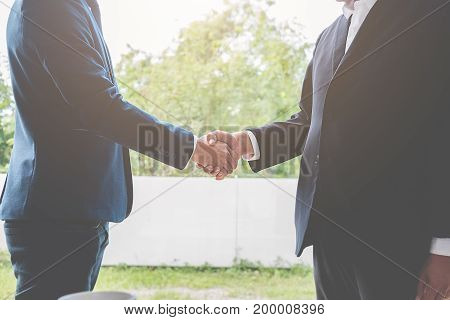 Successful businessmen handshaking after good deal. Business handshake and business people.Vintage tone Retro filter effect soft focus slow light.