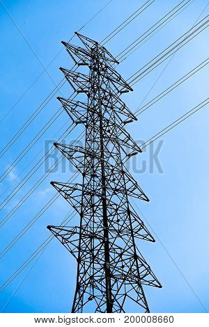 high voltage post power pole against blue sky