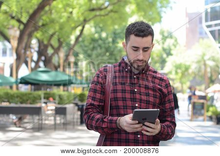 Attractive young man using digital tablet. Outdoors.