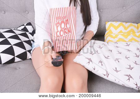 Young woman eating popcorn and watching movies relaxed on couch. Indoors.