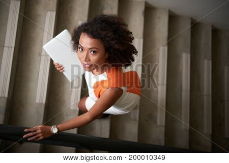 Business lady with laptop looking at camera when going up the stairs