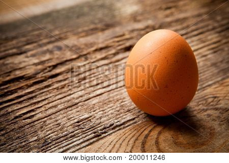 Egg In Rope Coil On Old Wooden Table