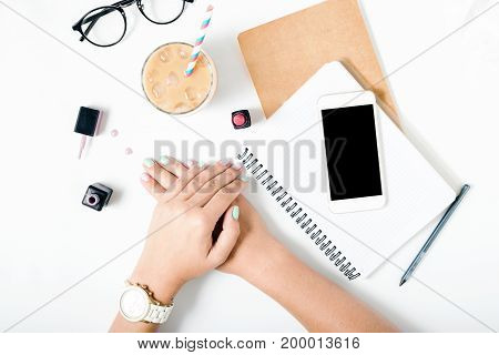 Flat lay hands of woman with beautiful summer manicure on white background close up top view