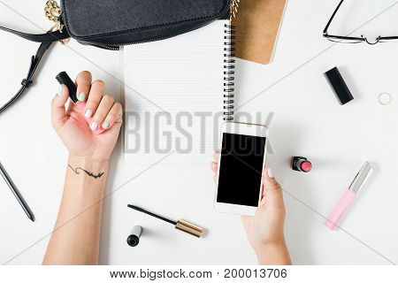 Flat lay hands of a woman with colorful summer manicure on white background top view