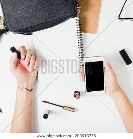 Flat lay hands of woman with colorful summer manicure on white background close up top view