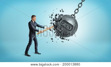 A small businessman smashes a giant swinging iron ball with a word DEBT on it using a hammer. Get out of debt. Reduce credit. Financial help.