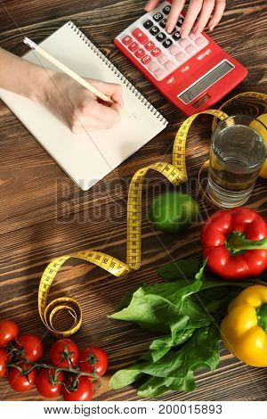 Young woman calculating calories at table. Weight loss concept