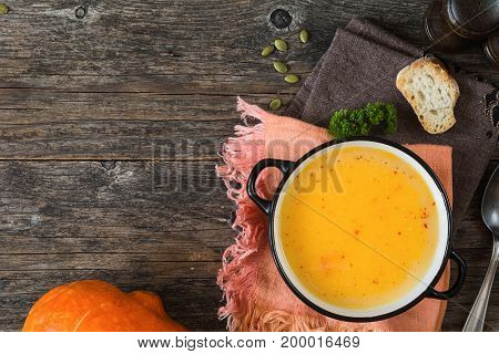 Bowl of pumpkin cream soup on napkin on rustic wooden table background. Top view and copy space for text