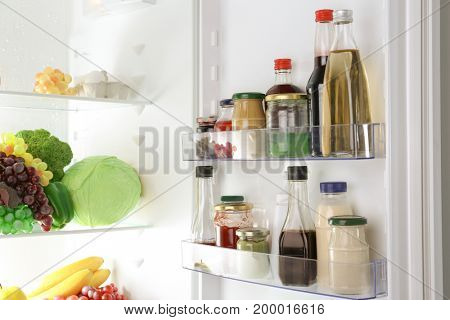 Different sauces on shelves in fridge