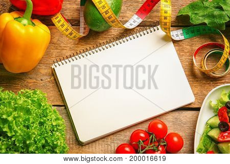 Empty notebook, measuring tape and set of healthy food on wooden table