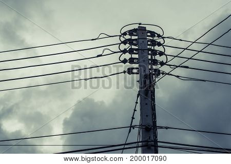 High Voltage Power Pole With Wires Tangled On Building Behind.