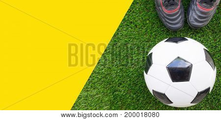 Soccer concept : Football (soccer ball) with old soccer boots on green grass background. Flat lay with yellow copy space.