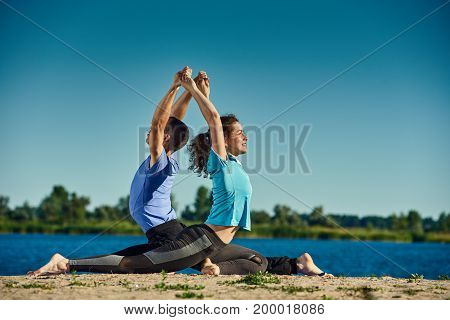 Healthy yoga couple practicing Kapotasana pose outdoors