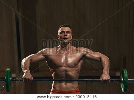 Portrait of strong muscular man working out with barbell