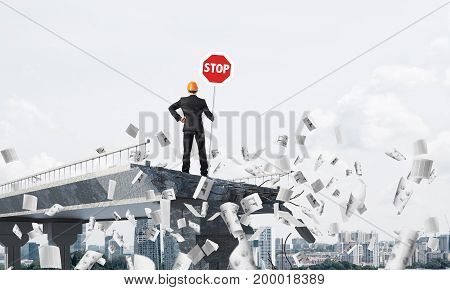 Rear view of engineer in helmet holding stop sign while standing among flying papers on broken bridge with cityscape on background. 3D rendering.