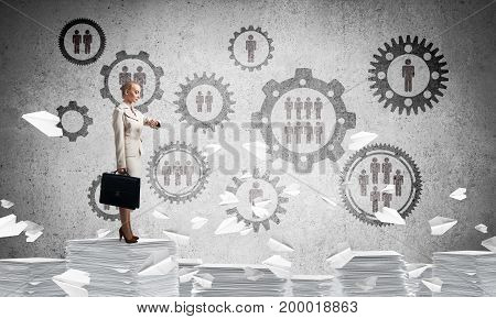 Business woman in suit standing on pile of documents among flying paper planes with social gear structure on background. Mixed media.