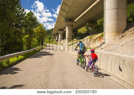 Tandem of father and daughter family cycling in Alpe Adria itinerary - Friuli-Venezia Giulia Italy