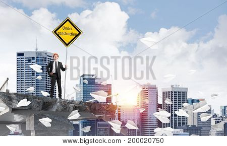 Young engineer in helmet holding under construction sign while standing among flying paper planes on broken bridge with cityscape and sunlight on background. 3D rendering.