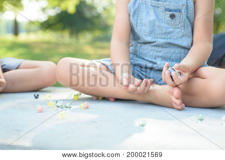 Boy playing marbles game outside on bright sunny day, having fun at summer break. Children activities.