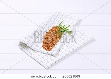 pile of raw buckwheat on checkered dishtowel