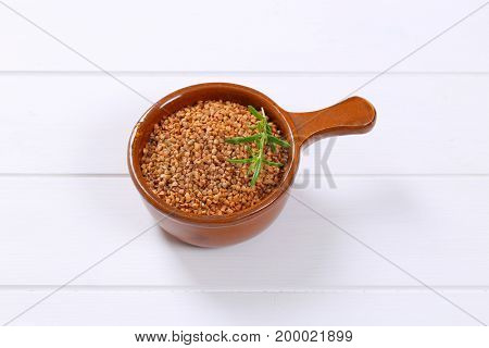 saucepan of raw buckwheat on white wooden background