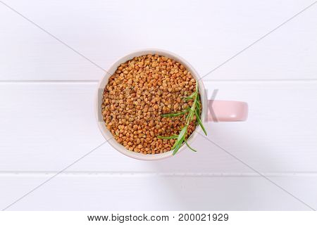cup of raw buckwheat on white wooden background