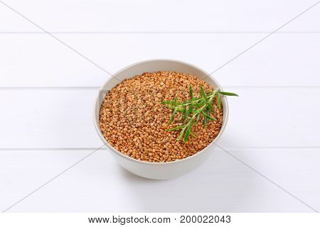 bowl of raw buckwheat on white wooden background