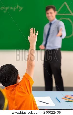 Schoolboy is willing to answer the question of the teacher
