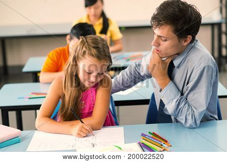 Young male teacher explaining schoolgirl how to draw an animal