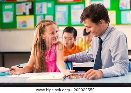Cheerful young teacher helping girl with homework