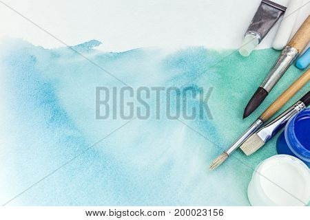 Artist Paintbrushes And Paints Over Abstract Green Watercolor Background On Textured Paper