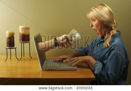 Hand & Money Coming Through Laptop Screen Toward Woman