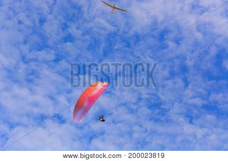Paramotor wing airman and motorless flying with a glider against blue sky.