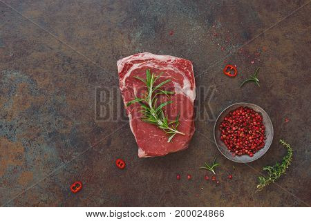 Fresh marbled meat  angus steak with spices on dark rustic background. Top view, blank space on the left side