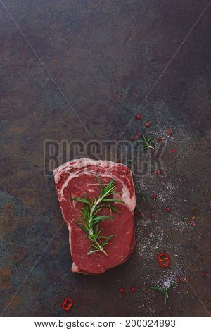 Raw beef steak garnished with rosemary, awaiting the oven. Rustic background, top view, lots of copy space