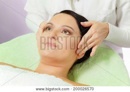 Woman enjoying head massage in spa, shallow depth of field