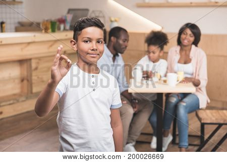 African-american Boy Showing Okay Sign With His Family Blurred On Background