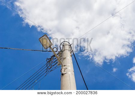 View on Power Lines in front of a cloudy Sky. Close-up of Power lines and a street lamp. Natural Background.