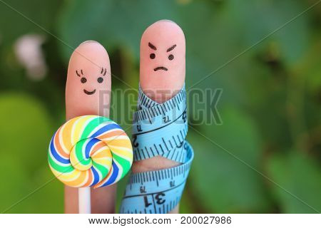 Finger art of couple with meter and candy. Concept of man angry because woman wants to lose weight.